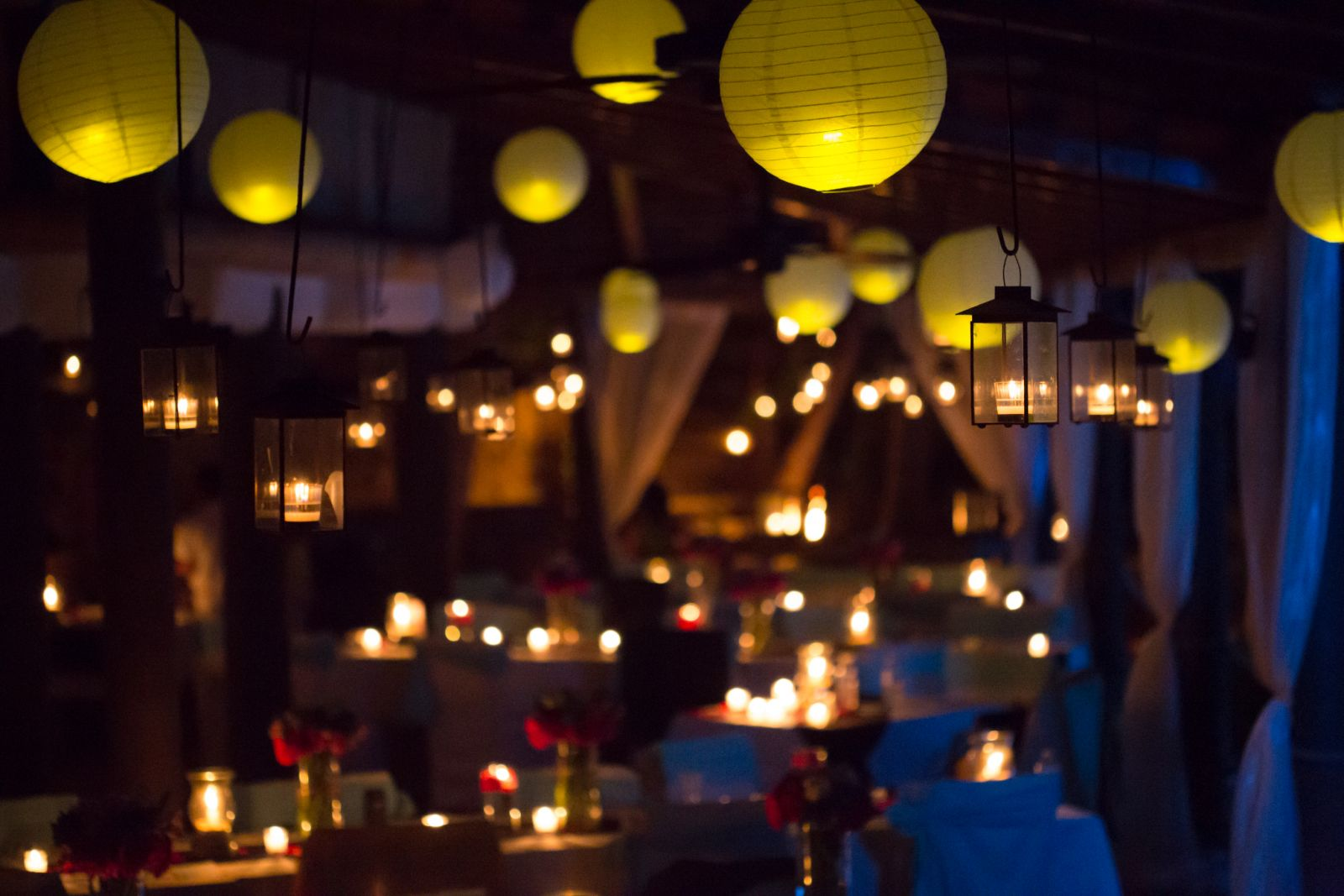 Chinese lanterns in warm color + beautiful candles around the wedding área