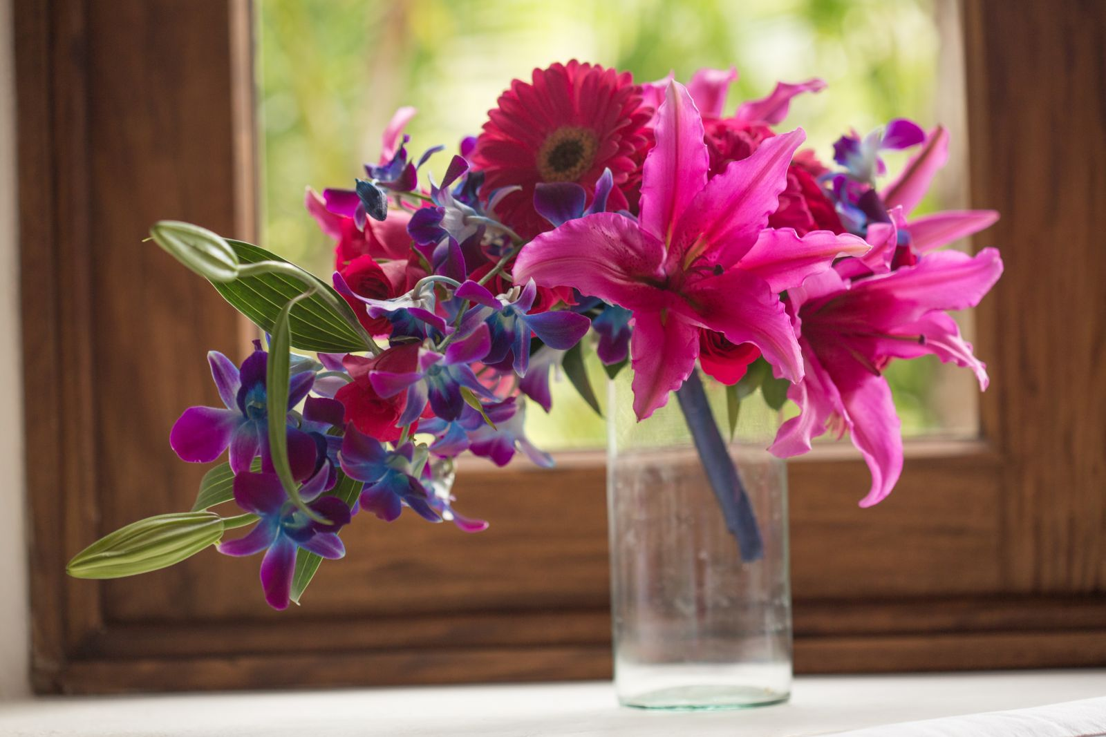 Tropical wedding bouquet with pink gerberas, lilies and a touch of purple