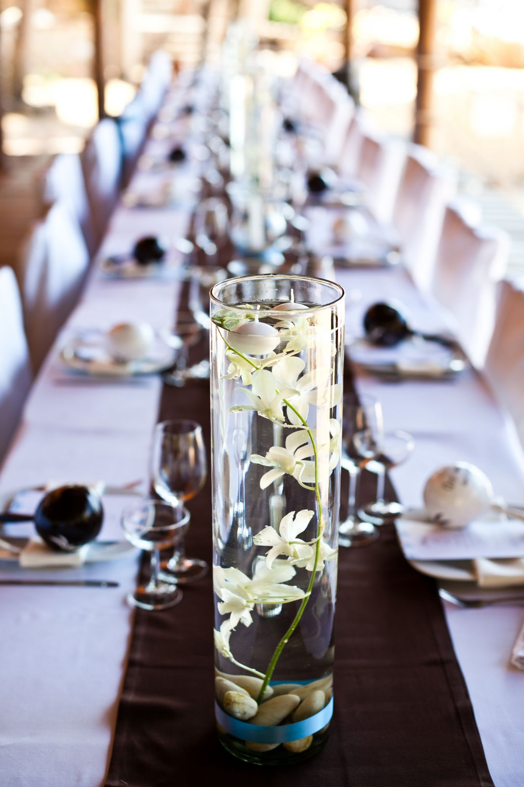 Floating candles and orchids for dinner centerpice
