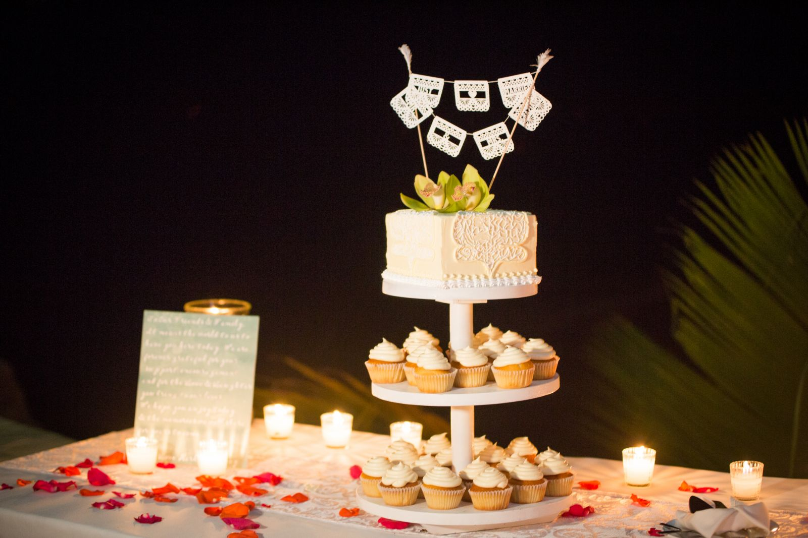 A top wedding cake and a combination of cupcakes