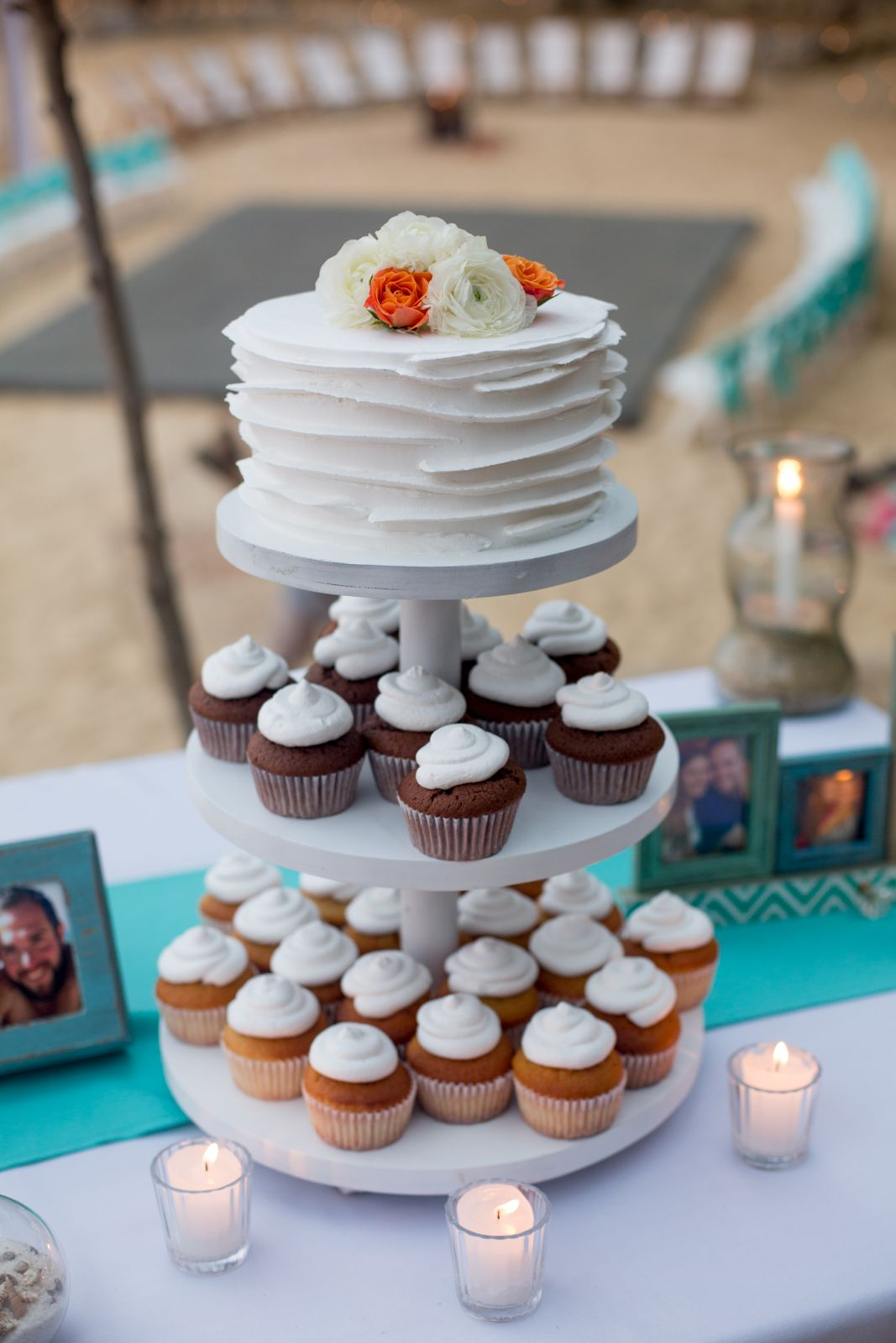 A silbolic wedding cake on the top and cupckes for erevyone