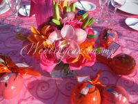 fyusha and orange centerpiece. Combination of  lilies, cymbidium orchids and fyusha roses