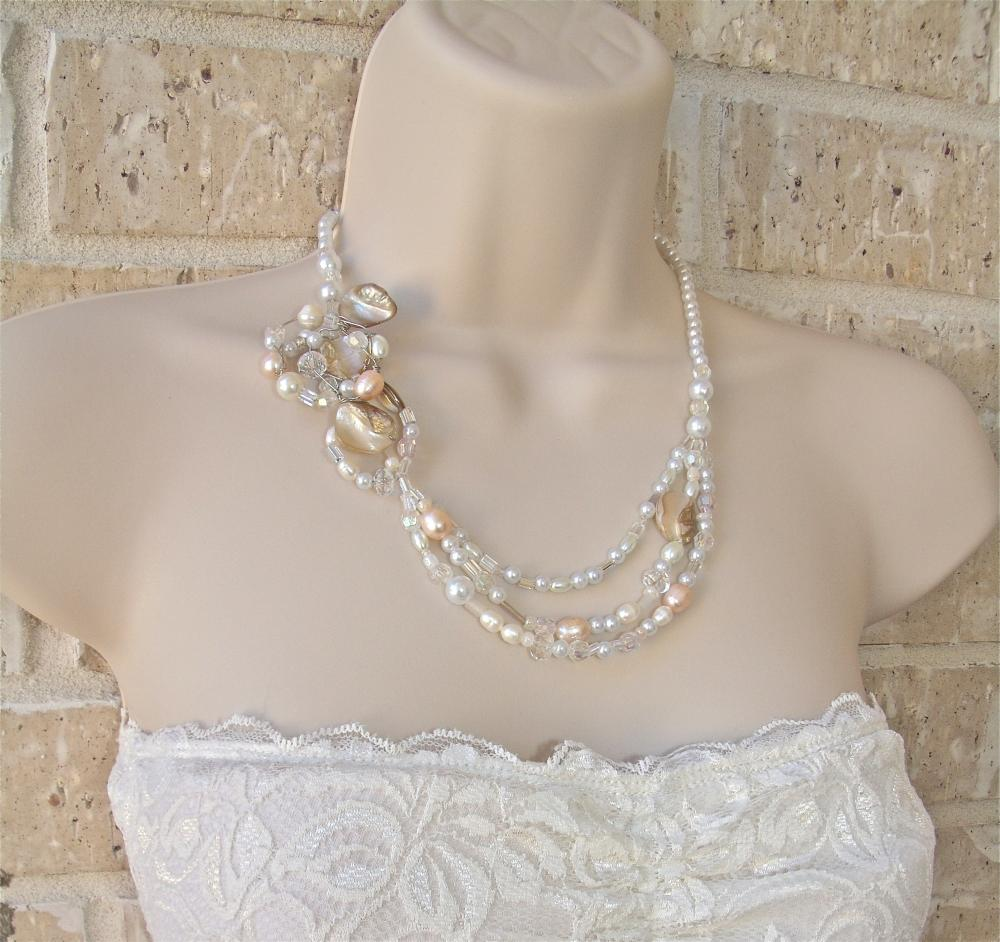 Mother of pearl natural shells, pale pink pearls and clear crystals have been united to form a tri-strand necklace with a handcrafted wire wrapped pendant that lies beautifully on the collar bone. Sparkle with this necklace for your walk down the aisle!