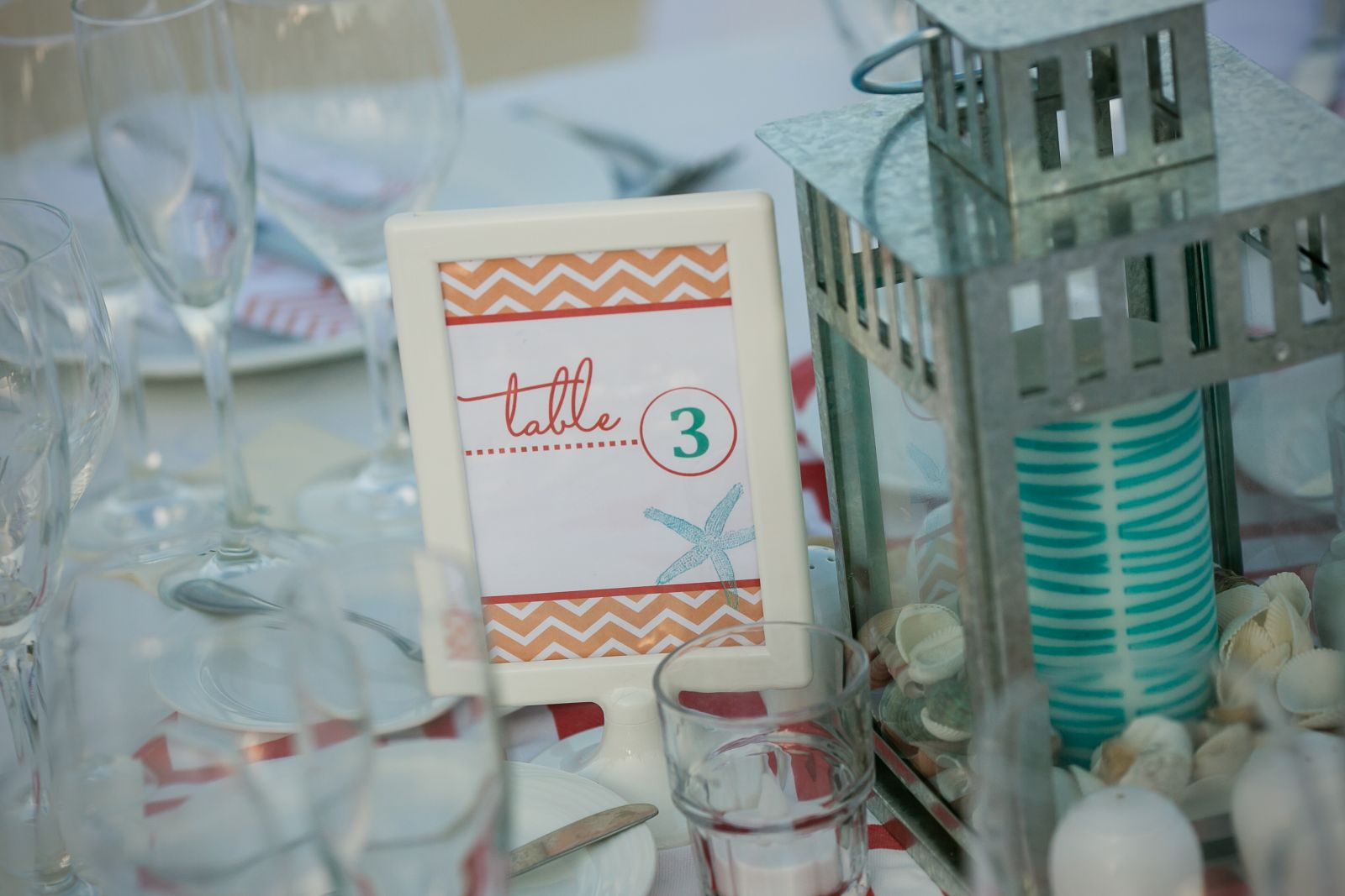 I designed the table numbers and then just printed in my home printer; then, put them in a .99 cent frame I got from IKEA (they were very easy to take with us and assemble on site!)  I also got the lanterns and candles from IKEA to create centerpieces.