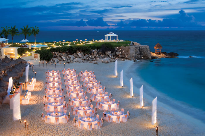 www.crystalwaterweddings.com Experienced travel agents who strongly value providing first class service and have a deep passion for destination weddings.  Dreams Cancun Resort & Spa.  Group dinner set up on the sandy-white beach with the magnificent weddi