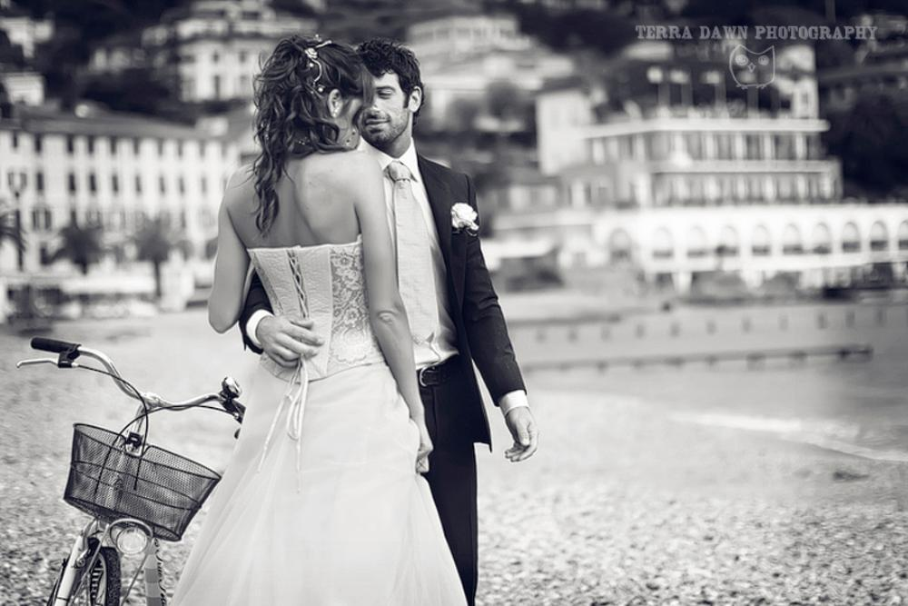 The bride and groom pose on the main beach in Santa Margherita, Italy.