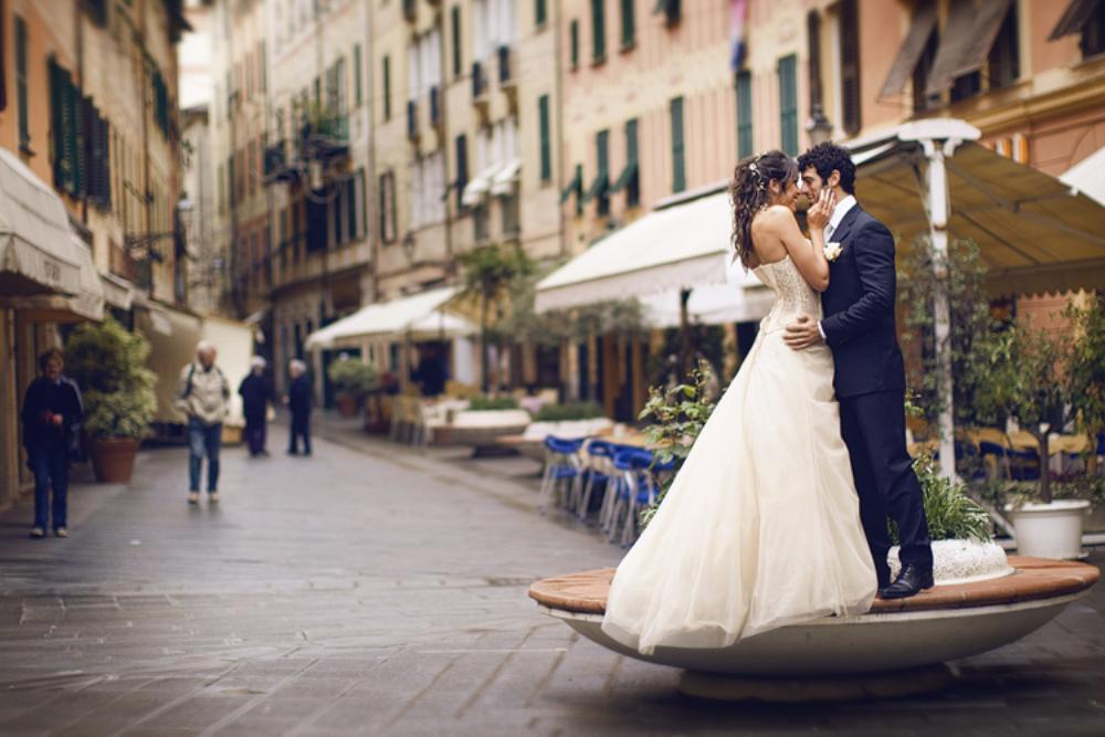 The bride and groom pose for portraits in the alleyway near the bakeries and markets of Santa Margherita, Italy.