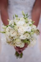 vintage bridal bouquet. A combination of white and ivory roses with white lisianthus and dashes of green lisianthus buds. Uneven, natural and organic type, wrapped with white satin ribbon.